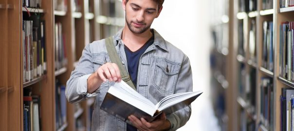 student reading library book